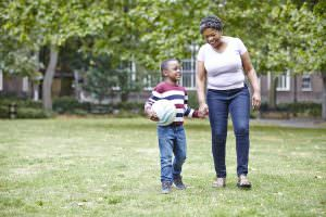 Post-adoption BME mother walking with son in park
