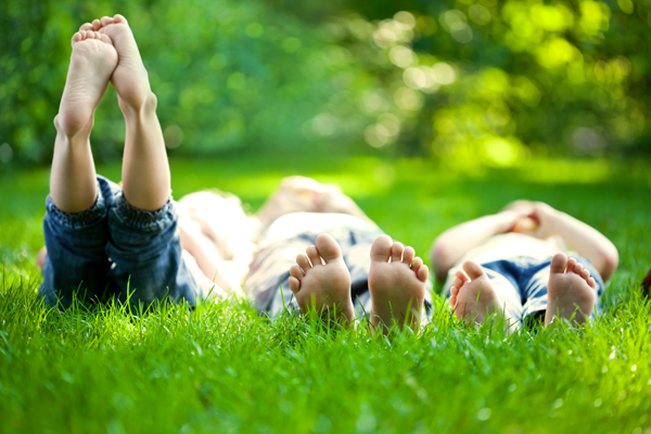 Adopted children lying in the grass with feet facing the camera