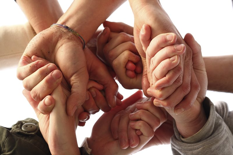 Group of sandy hands crossed holding each other