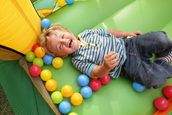 Little boy laughing on bouncy castle