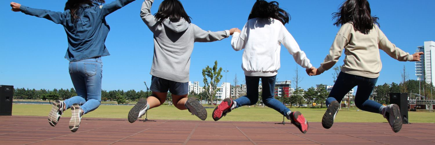 School girls jumping in the air on sports track