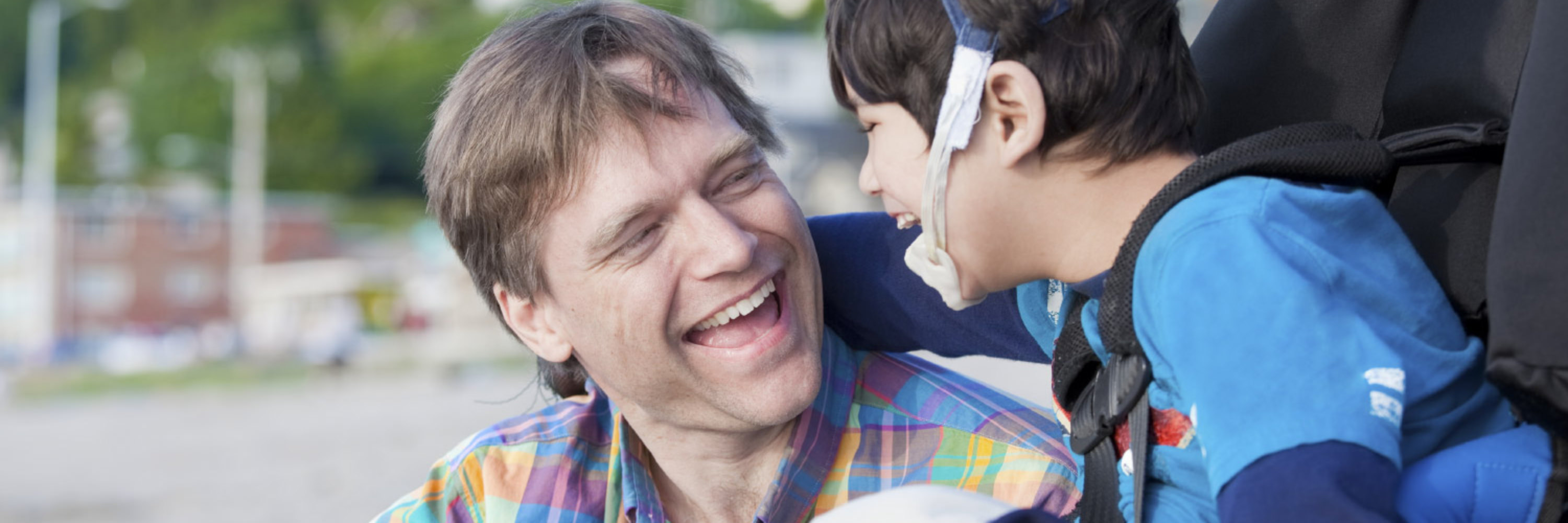 Adoptive father smiling with disabled son