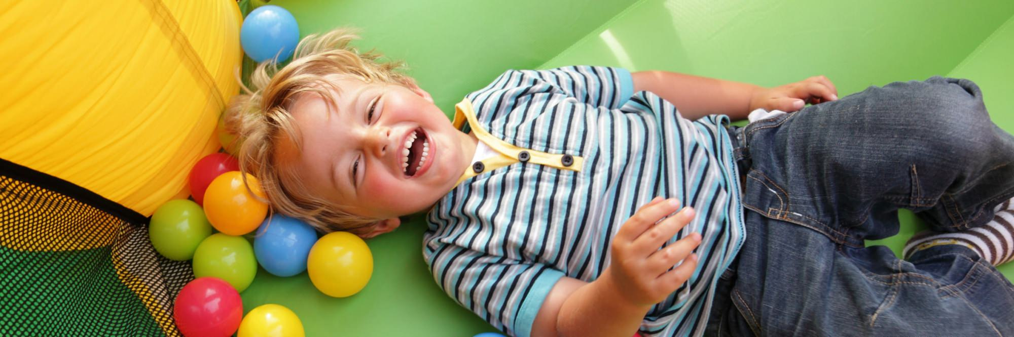 Adopted boy laughing on bouncy castle
