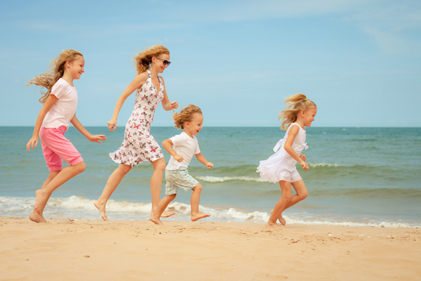 Adoptive family running on a beach
