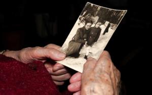 Elderly hand holding black and white photo