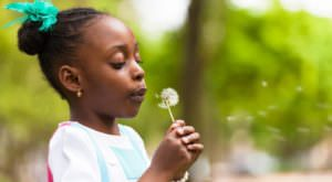 Little BME girl blowing dandelion seeds