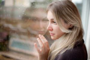 Woman looking at rain through a window