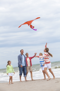 Adoptive family flying a kite on the beach