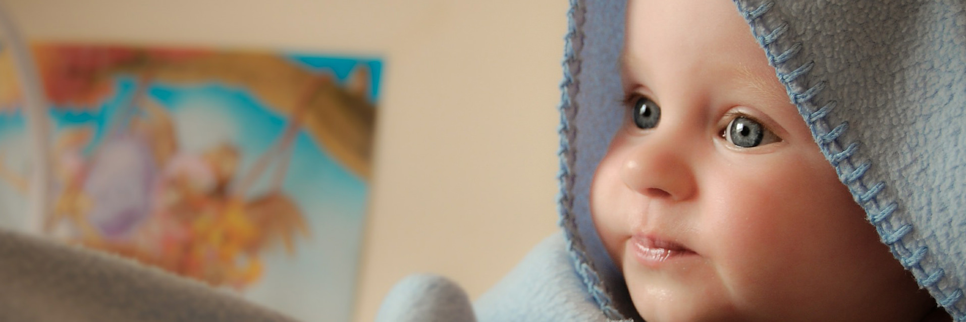 Blue eyed baby in hooded blue towel