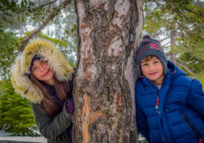 Adopted brother & sister wrapped up warm next to a tree